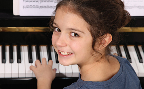 young girl taking piano lessons